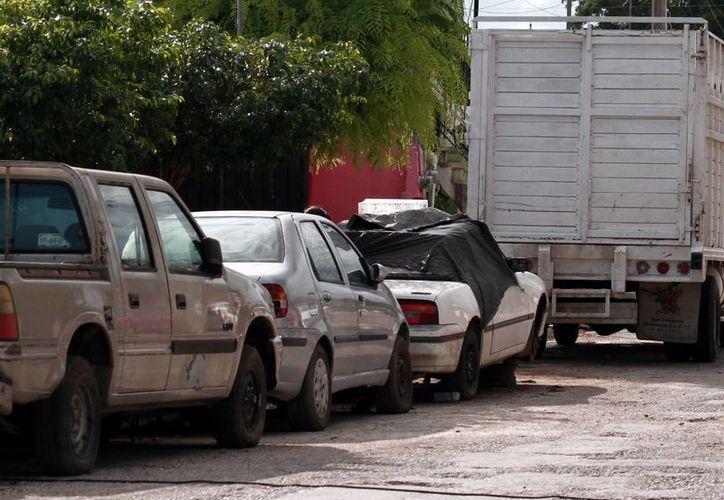 Muchos dueños prefieren llevar sus autos a talleres mecánicos que a distribuidoras automotrices. Imagen una fila de autos en uno de estos locales de reparación de vehículos. (Milenio Novedades)