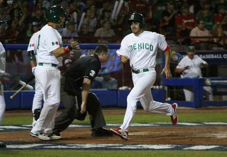 Esteban Quiroz (d), de la selección mexicana de béisbol, al anotar una carrera contra Nicaragua, durante la final de las eliminatorias del Clásico Mundial de Béisbol, en el estadio B-Air de Mexicali. (EFE)