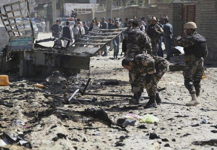 Miembros de las fuerzas de seguridad inspeccionan el escenario del ataque registrado en el aeropuerto internacional de Kabul. (EFE)
