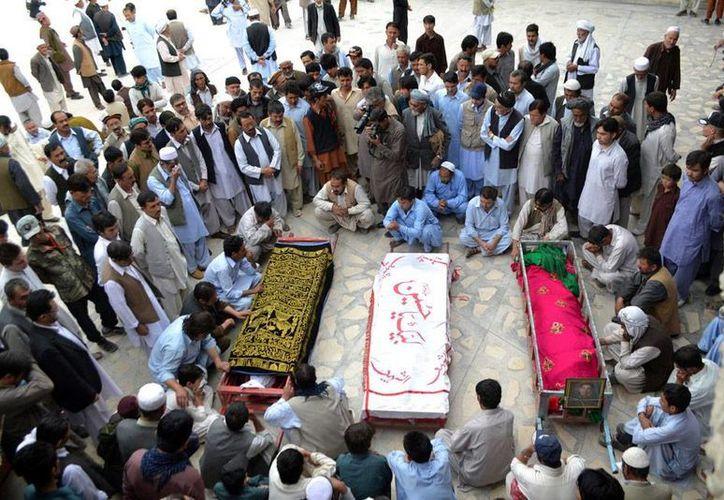 Deudos se reúnen en torno a los féretros de algunas de las víctimas de una matanza en Pakistán, en la que murieron 8 personas de la etnia hazara. (Efe)
