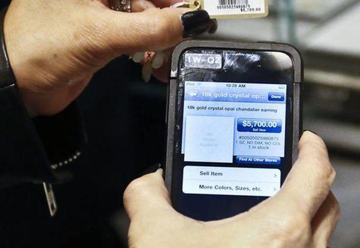 Un vendedor de Barney's New York usa un iPod Touch para ayudar a registrar la compra de un cliente. (Agencias)