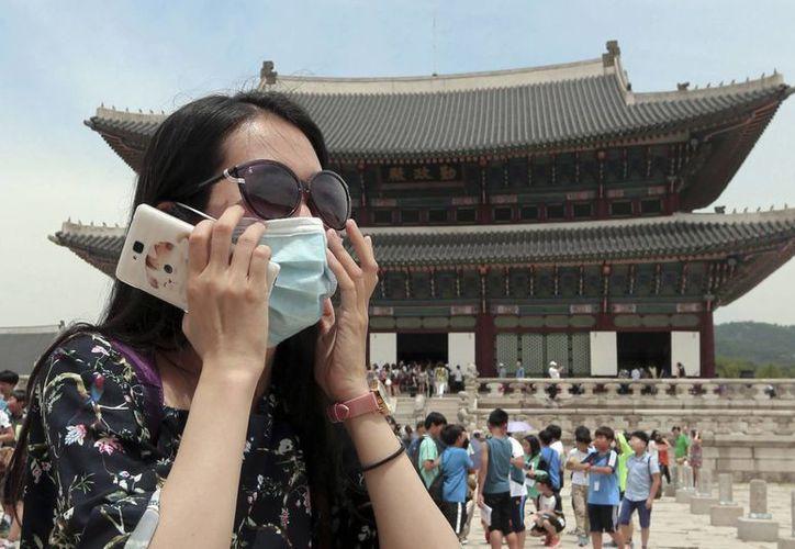Una turista china no identificada porta una mascarilla a manera de prevención contra el Síndrome Respiratorio del Medio Oriente (MERS por sus siglas en inglés) mientras visita el Palacio de Gyeongbok en Seúl, Corea del Sur. (Choi Jae-koo/Yonhap vía AP)