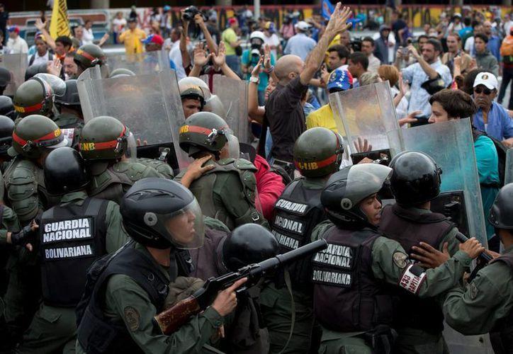 Soldados de la Guardia Nacional Bolivariana bloquean a un grupo de manifestantes que protestaban en contra del gobierno de Maduro. Exigen a las autoridades electorales contar las firmas que podrían conducir a un voto revocatorio presidencial. (Foto AP / Fernando Llano)
