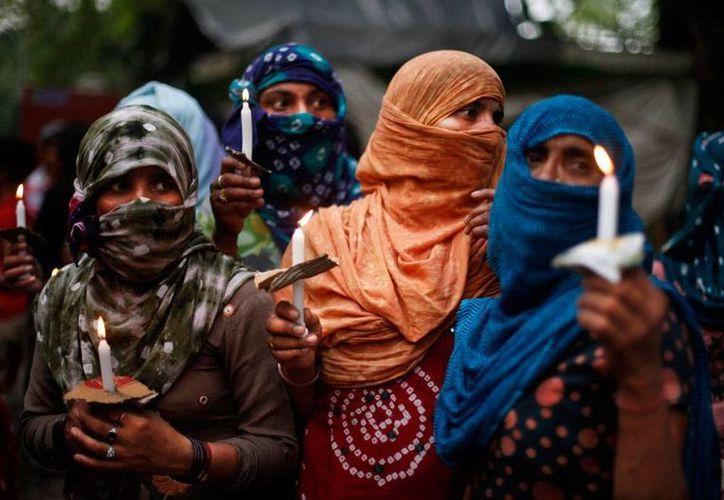 Activistas de India cargan velas durante una vigilia por las niñas que fueron violadas y colgadas por un grupo de hombres. (AP)
