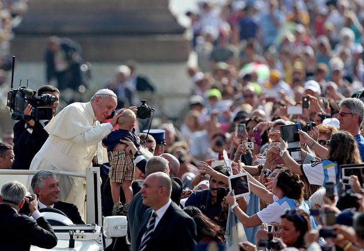 El Papa Francisco bendice a un bebé a su llegada a la audiencia general de los miércoles en la plaza de San Pedro del Vaticano. (Archivo/EFE)