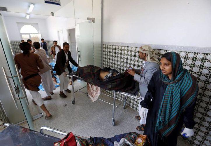 Yemeníes observan los cuerpos de las víctimas de varios ataques con explosivos contra dos mezquitas chiíes en el norte y el centro de Saná, en Yemen, este viernes 20 de marzo de 2015. (EFE)