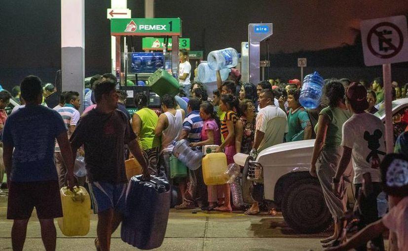 Con el anuncio del aumento a los precios de la gasolina en el primer día de 2017, cientos de personas intentaron abastecerse de combustible antes de que subiera su precio en un 20 por ciento. (Archivo AP/Erick Herrera)