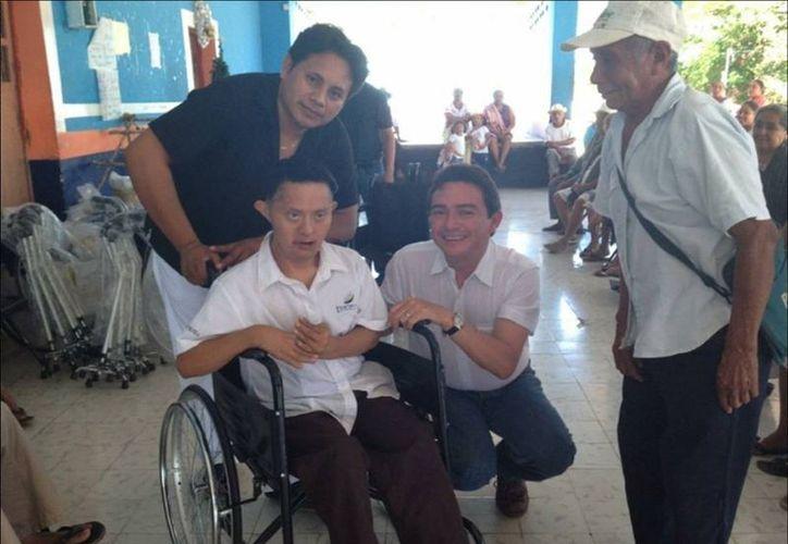 Este joven de Hocabá, que padece síndorme de Down, podrá moverse ahora con la silla de ruedas que recibió.  (Cortesía)