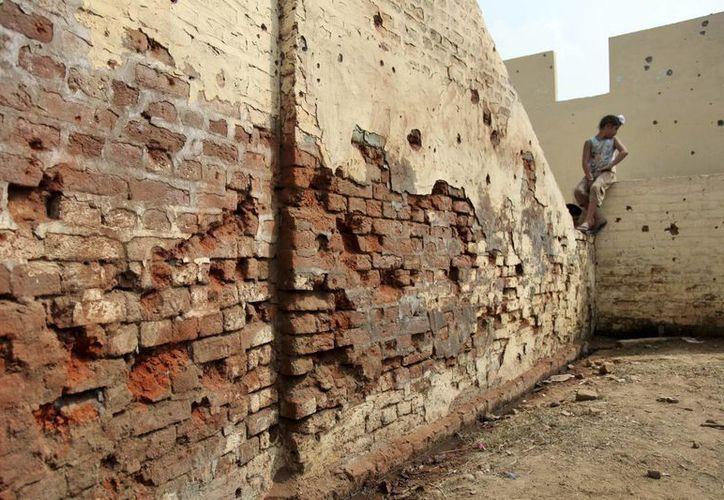 Un niño indio se sienta sobre el muro de una casa con orificios de disparos supuestamente provenientes del lado paquistaní de la frontera en el pueblo de Flora, en Ranbir Singh Pura, a 35 kilómetros de Jammu, India. (Agencias)