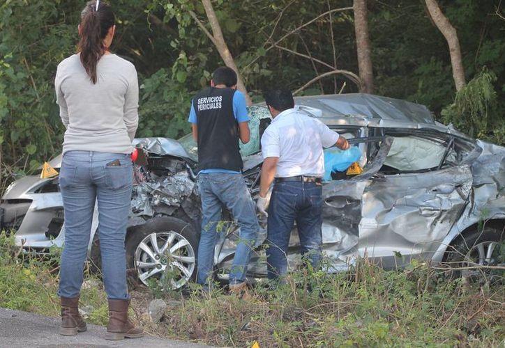 Agentes de los Servicios Periciales de la FGE toman dato del accidente, en donde el conductor del Mazda quedó prensado. (Milenio Novedades)