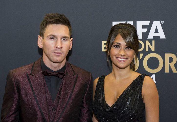Messi con su estrafalario atuendo junto a su pareja durante la entrega del Balón de Oro. (Foto: AP)