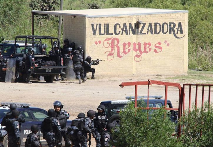 Associated Press publicó esta imagen que muestra a policías usando armas durante el desalojo de Oaxaca. (Agencias)