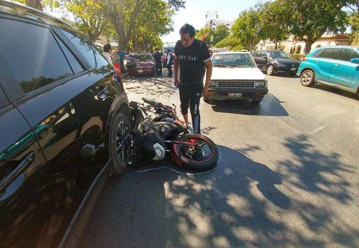 El conductor de la motocicleta miraba incrédulo su vehículo debajo de las llantas de una camioneta. (José Acosta/Milenio Novedades)