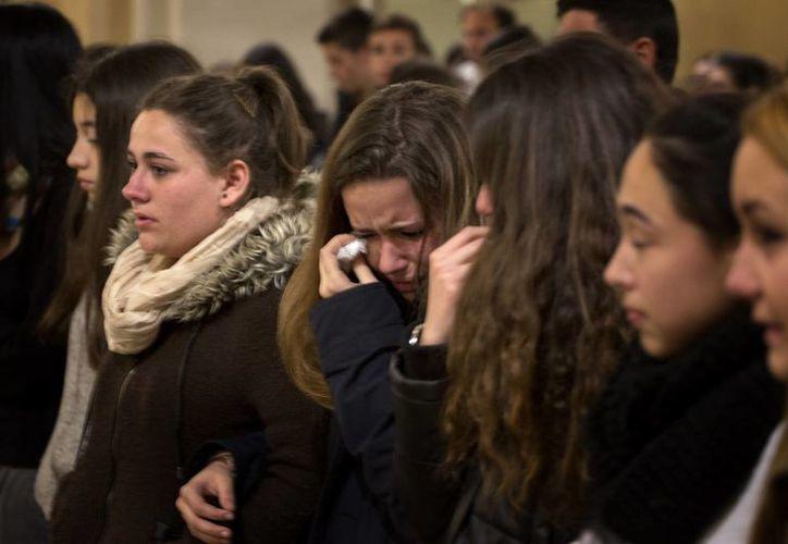 Amigos de los estudiantes alemanes que viajaban en el avión estrellado asisten a una misa en Llinars del Vallés, cerca de Barcelona, España. (Agencias)
