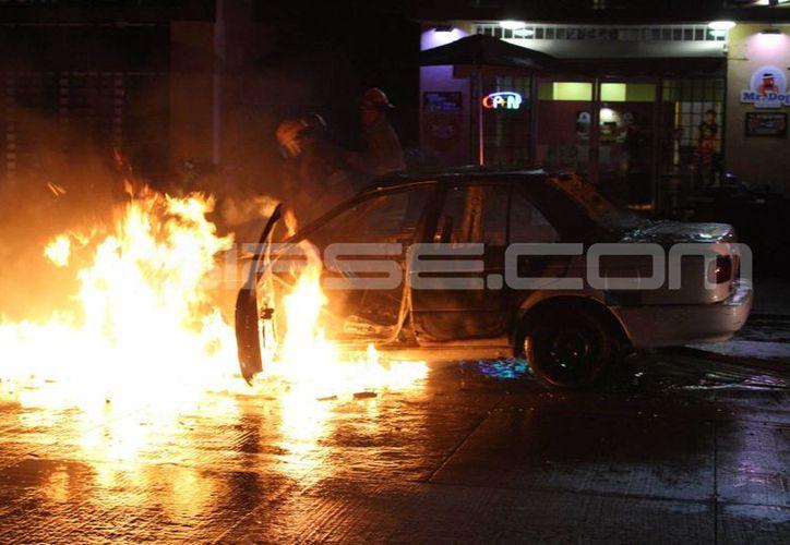 Un taxi ardió en llamas ayer en la avenida CTM de Playa del Carmen. (Redacción/SIPSE)