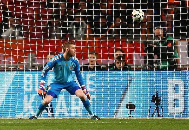 El portero de España, David de Gea, observa cómo el balón entra a su portería. La Roja cayó 2-0 en su visita a Holanda, dentro de las eliminatorias de la Eurocopa 2015. (AP)