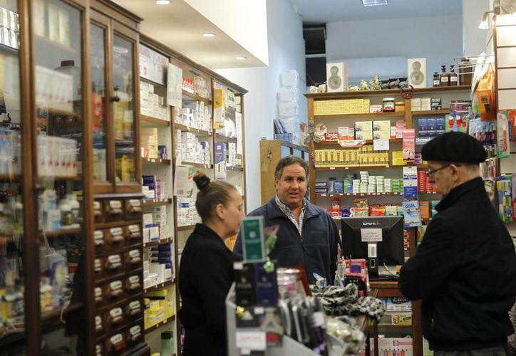 Un cliente compra en la farmacia 'Dr. Ocasión', en la Ciudad Vieja de Montevideo, Uruguay. Pocas farmacias empezarán con la compraventa de marihuana. (EFE/Archivo)