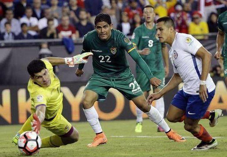 El portero boliviano Carlos Lampe salva un gol ante el acoso de Alexis Sánchez, pero al final Chile ganó 2-1 con un penal cobrado por Arturo Vidal en la Copa América Centenario. (AP)