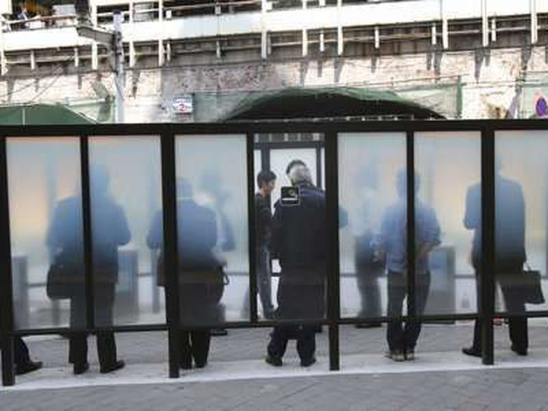 People smoke at a designated area in Tokyo. Japan has approved its first national legislation banning smoking inside of public facilities.