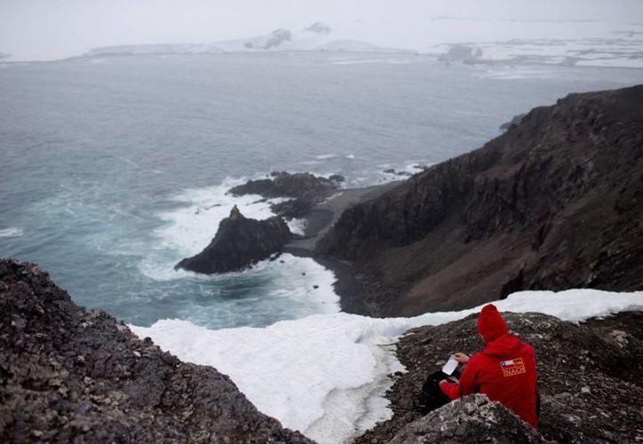 El científico alemán Andreas Beck toma notas en la isla Robert, en el archipiélago de las islas Sethland del Sur, en la Antártida. (Agencias)