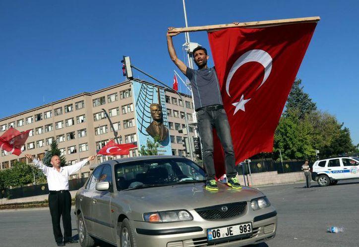Un hombre agita una bandera turca durante una protesta contra el golpe de Estado. (Agencias)