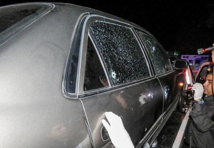 En la foto se ve a policías forenses examinando el auto donde se encontraba la actriz, modelo y exMiss Venezuela Mónica Spear Mootz, en la autopista que comunica a Valencia y Puerto cabello en el Estado Carababo de Venezuela. (EFE)