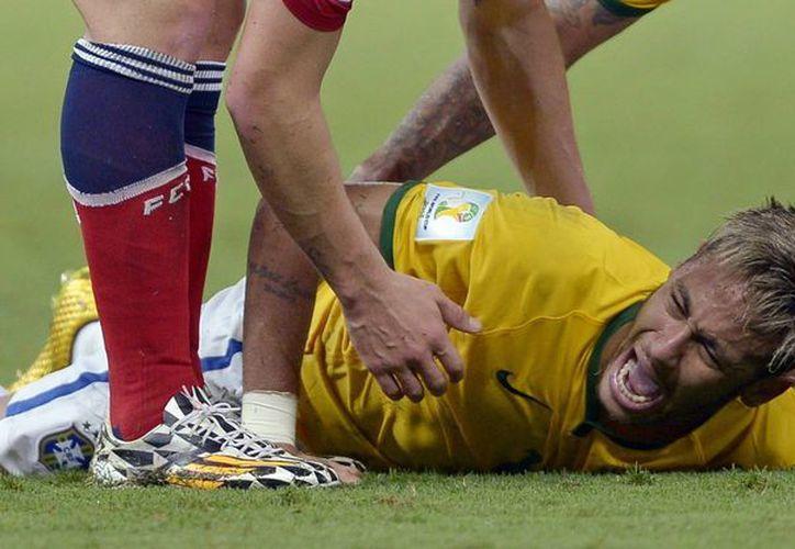 Neymar se duele tras recibir una patada por la espalda que lo dejó fuera del partido Brasil vs Colombia y del Mundial. (Foto: AP)