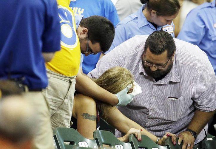 Atención a una aficionada que recibió un pelotazo en la cabeza durante un partido de Grandes Ligas entre Cerveceros y Bravos. (Foto: AP)