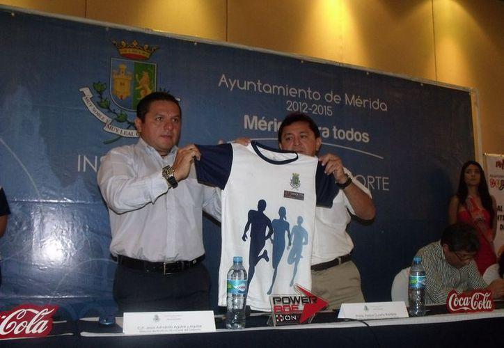 Jesús Aguilar y Felipe Duarte presentan la playera oficial del maratón. (SIPSE)