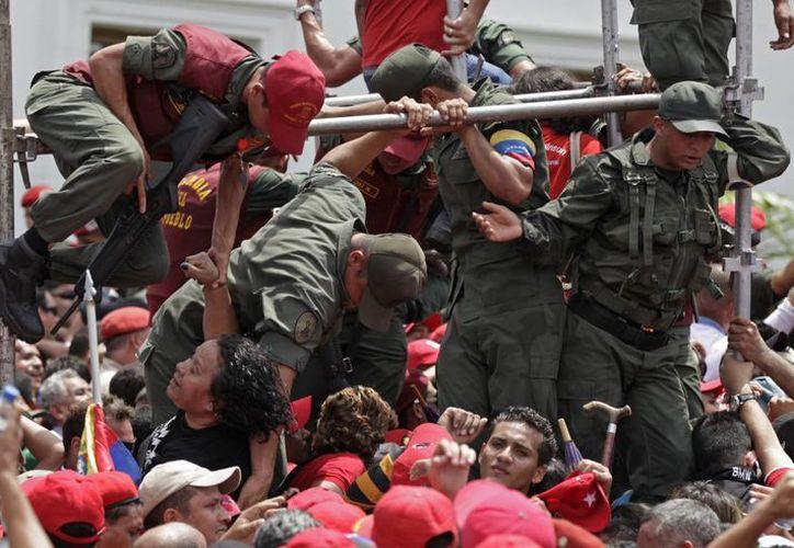 Miles de simpatizantes del presidente de Venezuela, sufren el drama de su muerte, incluso ya han causado desmanes por tal de ver su féretro. (Agencias)