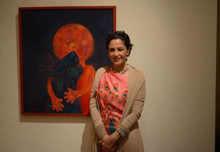 Mercedes Zaragoza junto a una de las obras que presenta en el Callejón del Congreso, en el Centro de Mérida. (Luis Pérez/SIPSE)