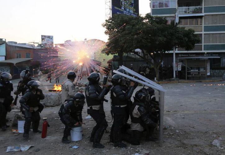 La Policía Nacional Bolivariana se protege al explotar un cohete de artificio lanzado por manifestantes antigubernamentales durante enfrentamientos en Caracas, Venezuela. (Agencias)
