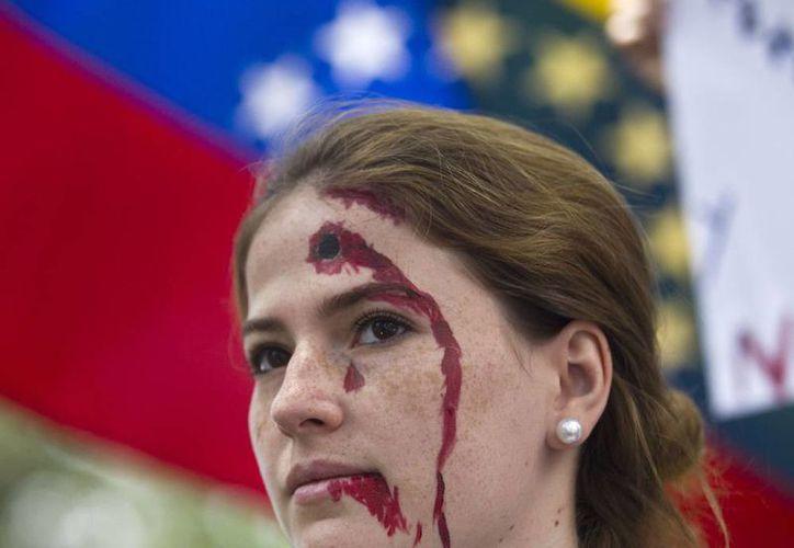 Las protestas en Venezuela cobraron la vida de otra persona. La imagen corresponde a una Una ciudadana antigobiernista -quien simula con maquillaje un disparo en la frente-, durante una manifestación frente a las oficinas de la Organización de Estados Americanos, en Caracas. (Agencias)