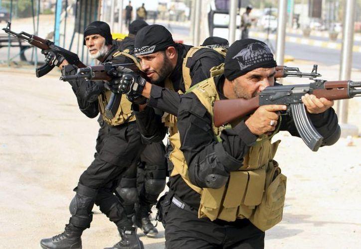 Hombres chiítas, obligados por la avanzada del Estado Islámico a dejar su localidad natal de Tel Afar, participan en un desfile al terminar su entrenamiento militar en Karbala (Irak), el pasado 2 de octubre. (EFE/Archivo)
