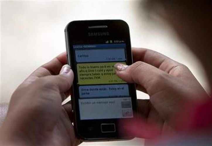 Una mujer usa su teléfono celular en Camajuaní, Cuba, el 3 de marzo de 2014.  (Agencias)