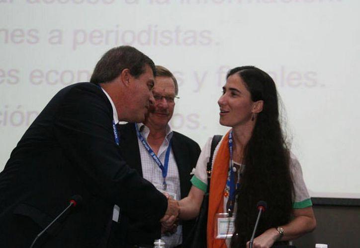 La bloguera cubana Yoani Sánchez, al terminar su intervención, le acompaña el el presidente de la SIP, Jaime Mantilla (c). (sipiapa.org)