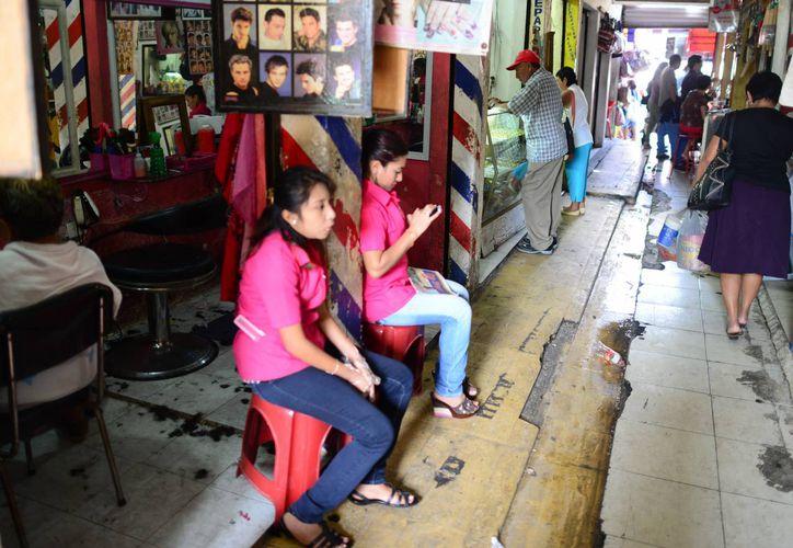 La empresa Manpower señala que en Yucatán hay buenas expectativas laborales para 2015. Imagen de un par de mujeres en las puertas de una estética.(Milenio Novedades)
