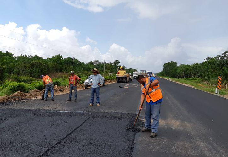 Diez kilómetros del tramo carretero Limones - Felipe Carrillo Puerto reciben mantenimiento por parte de trabajadores de la SCT. (Enrique Mena/SIPSE)