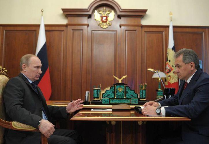 El presidente ruso, Vladimir Putin habla con el ministro de Defensa, Sergei Shoigu, a la derecha, durante una reunión en el Kremlin de Moscú. (Agencias)