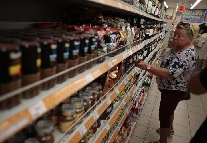 Una mujer realiza compras en un supermercado venezolano, donde es evidente la escasez de productos, de ahí la prohibición de exportación decretada por el Gobierno. (Archivo/Agencias)