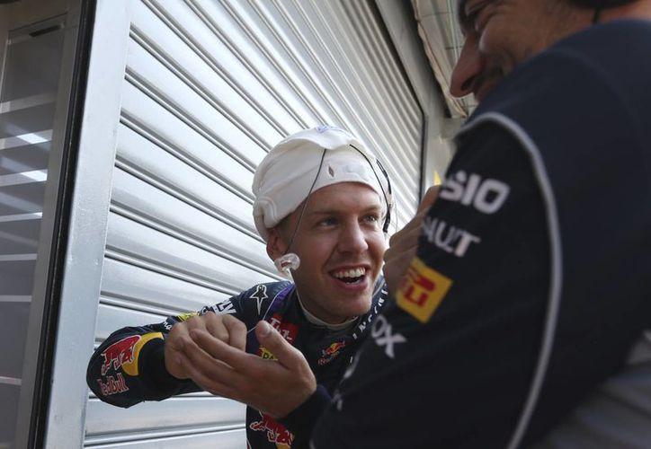 Vettel (centro) dialoga con un mecánico durante una prueba. (Agencias)