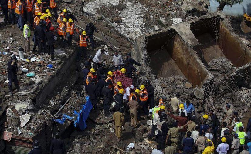 Miembros de la Fuerza de Respuesta ante Desastres Naturales (NDRF) recuperan  el cadáver de una mujer tras el derrumbe. (EFE)