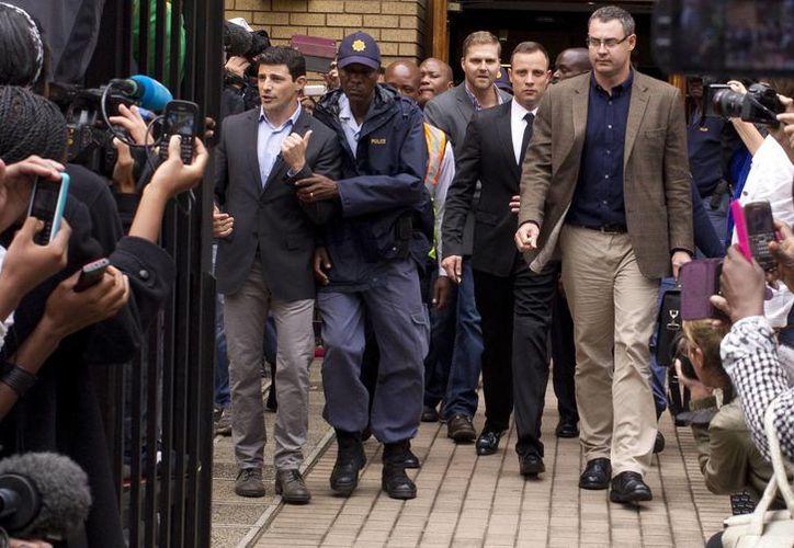 Pistorius (de traje negro) abandona el Tribunal Superior de Pretoria tras una jornada más del juicio que se le sigue por asesinato. (EFE)