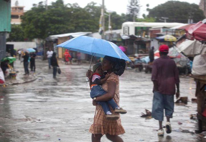 Una mujer que lleva un niño camina bajo la lluvia provocada por el huracán 'Matthew' en Port-au-Prince, Haití. (AP/Dieu Nalio Chery)