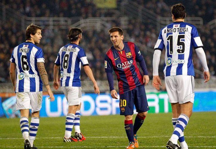 El delantero del Barcelona, Lionel Messi (de frente), está en medio de la tormenta por supuestas diferencias con el técnico Luis Enrique, lo que ha difundido el rumor de que el Chelsea está pugnando por sus servicios. (Archivo/Efe)