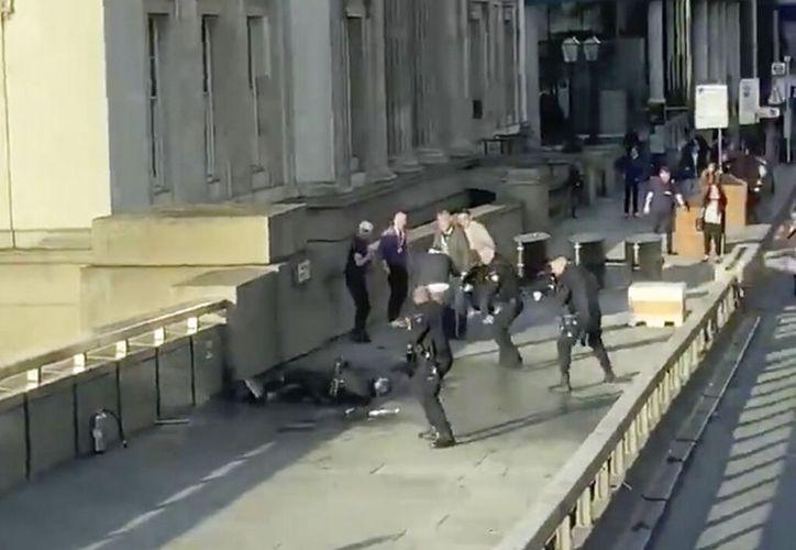 En esta imagen tomada de un video difundido por @HLOBlog, varios policías rodean a un hombre después de un incidente en el Puente de Londres, el viernes 29 de noviembre de 2019. Un hombre que llevaba un chaleco explosivo falso apuñaló a varias personas antes de ser derribado por la gente y luego muerto a tiros por los agentes armados, informaron la policía y el alcalde de la ciudad. (@HLOBlog vía AP)