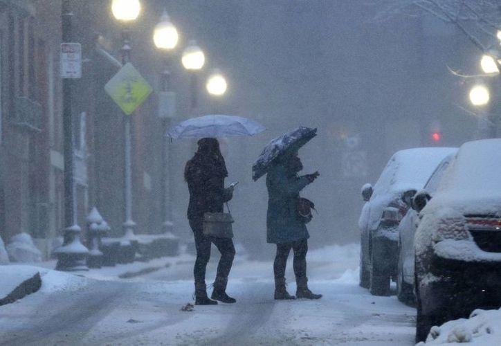 Personas se cubren con sombrillas de la nieve que cae en el vecindario de North End en Boston, el domingo 15 de marzo de 2015.(Foto: AP/Steven Senne)