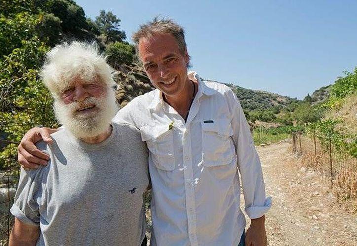 Dan Buettner (der) junto a Mihalis Gerakis un habitante de  Salinus, en la isla italiana de Cerdeña, lugar donde acostumbran beber vino tinto con frecuencia. (facebook.com/dan.buettner1)