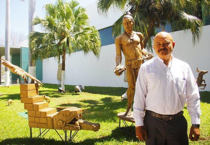 """En la foto el escultor Reynaldo Bolio Suárez y de fondo parte de sus obras de la exposición """"El eterno Mayab"""". (Juan Albornoz/SIPSE)"""