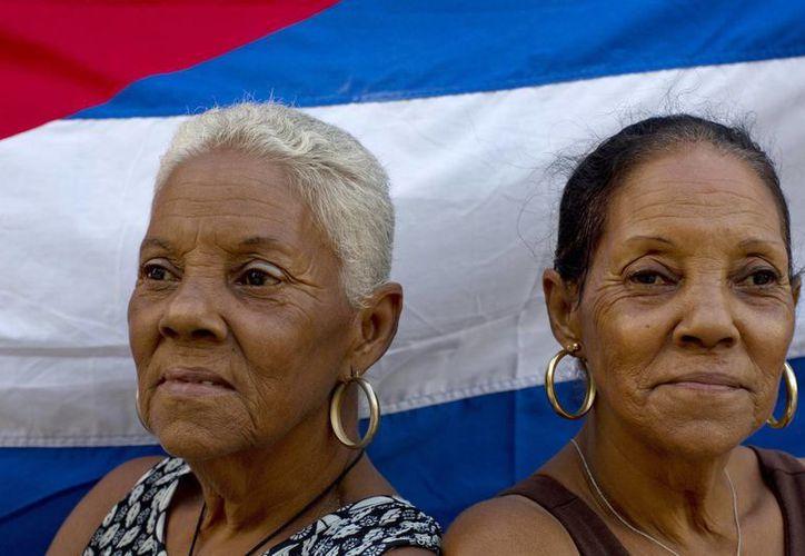 Las hermanas gemelas Fe Fernández, (izq) y Esperanza, de 65 años, posan frente a una bandera cubana en la calle donde viven en La Habana. (Agencias)